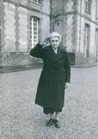Woman standing and saluting while looking towards the camera and smiling.