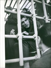 Man talking to prisoner across a cage.