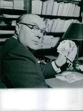 Paul Henri Spaak playing cards, looking back at the camera.