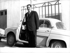 Algierian standing beside the automobile in Paris during the Algerian Revolution