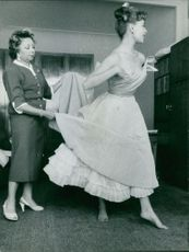 A woman adjusting another woman dress.