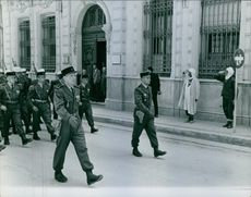 Soldiers marching in the street, while people standing on sidewalk saluting them.