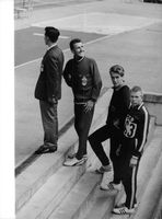 Donald Arthur Schollander standing on the stairs with his fellow athletes.