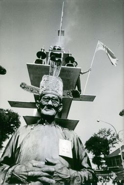 Low angle view of an old man, a soldier at his back, standing at the watch tower, holding a flag, in Saigon, Vietnam, November 1972.
