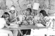 Claudia Cardinale enjoying drink, with people.