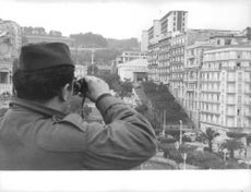 A soldier looking at the hotel using a binocular, in Algeria, 1960.