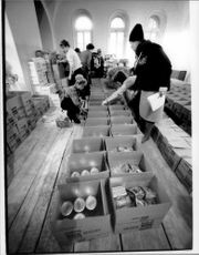 Inside the church, women pack cans with Swedish defense's corned beef, Swedish butter, Chilean powder soup and Italian pasta in detergent cartons
