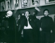 A man screaming and other people looking at him during an event.