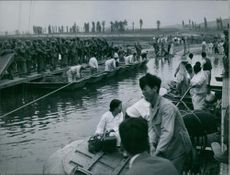 Civilians on a boat beside the docks where soldiers stand carrying rifles, 1950.