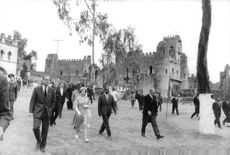 Elizabeth II and prince Philip walking with people, on visit to Ethiopia.