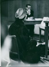 """Woman sitting in a courtroom and looking at something.  """"__ proceeding""""  1960"""