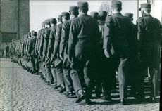 1970 Soldiers lined up together in front of an officer marching.