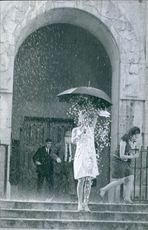 Liselotte Pulve holding an umbrella in the rain. 1966.