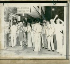 Holidaymakers at Torremolinos forming a late-night queue outside a food shop because they had not been served with meals at their hotels during the strike by Spanish hotel staff.
