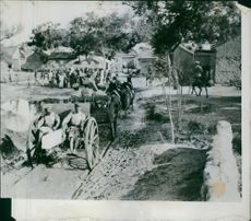 Horse cart passing by the street, people gathered in street looking at it.