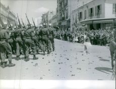 Soldiers marching in street during an event after the France war, 1962.