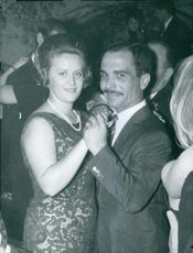 Man and woman looking towards the camera while dancing in a party.  1964
