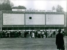 People gathered in front of a board displaying the match scheduled for the Canada World Cup 1963.