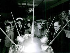 Alexey Arkhipovich Leonov standing and looking at machine