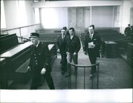 Men and policemen walking in the courtroom.