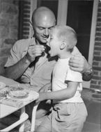 Yul Brynner with a child, eating.