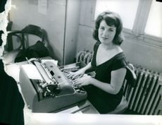 Woman working on typewriter.1961