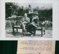 Former British Prime Minister Stanley Baldwin sitting in a bench with his fiance Lucy Baldwin, while their son Oliver Baldwin is reading something behind of them