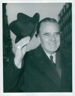 Portrait of Averell Harriman with his hat lifted in greeting with a smile