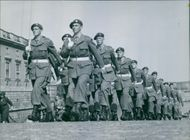 Soldiers holding and walking together in a row.