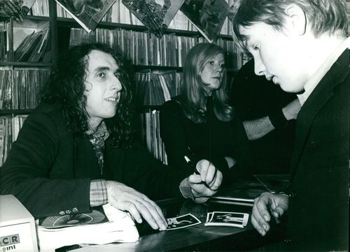 Tiny Tim signing photographs