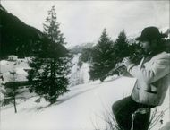 Karl Schranz playing flute in the Alps.