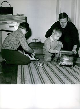A father playing toys with his two young boys.