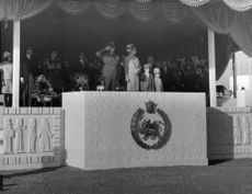 Mohammad Reza Shah Pahlavi along with Farah Pahlavi and kids standing on a podium.