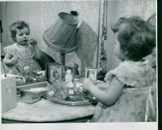 Girl looking herself in mirror and grooming.