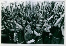 Soldiers standing and shouting together, holding gun.