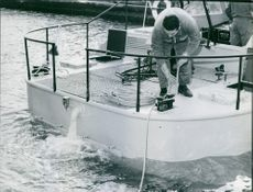 Man holding rope and operating on the boat. 1971