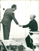 Henry Kissinger shakes hands with Le Duc Tho at a meeting in Paris