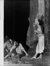 A woman in costume, leaning on the wall, holding a flower, men looking at her, in Bali, Indonesia, January 2, 1962.