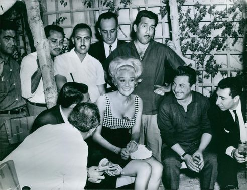 Group of men gathered around Lesley Langley. 1966.
