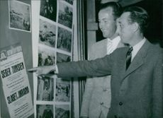 Two men communicating with each other and smiling while pointing towards a poster.