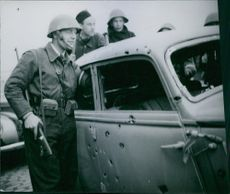 German occupation in Denmark Military men inspecting the car pierced by several bullets and shrapnel.