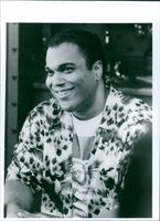 """Kamal Ahmed sitting and smiling in movie """"The Jerky Boys""""."""