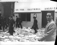 People walking on a street full of scattered trash during the Algerian War, 1960.