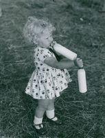 A toddler, standing and drinking milk from the feeding bottle, with her other hand holding another bottle, 1962.