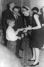 Queen Paola holding Prince Laurent's toy gun. 1967