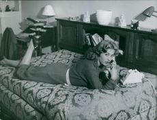 Woman lying on the bed and talking on a telephone.