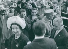 A photo of Queen Margarita of Bulgaria smiling wearing a beautiful white hat while press people are busy taking images.