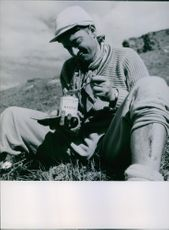 A man sits on the ground while eating a canned goods.