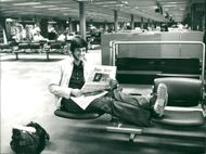 Sebastian Coe is reading a newspaper at the airport
