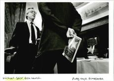 Michael Spicer standing while talking to the man holding a book.